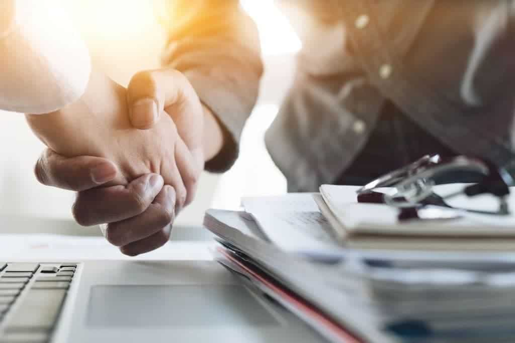 Shaking Hands agreeing an OIC which is one of the options under the IRS tax relief programs that will give you a Fresh start without using an IRS tax attorney
